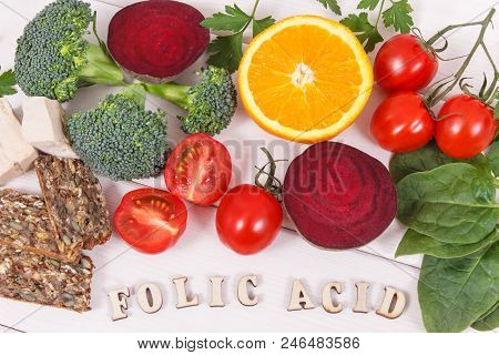 Inscription folic acid with nutritious products containing vitamin B9, natural sources of minerals and folic acid, concept of healthy nutrition poster