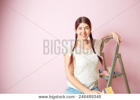 Picture Of Cheerful Woman With Brush Next To Stepladder And Roller Against Blank Pink Wall. Place Fo