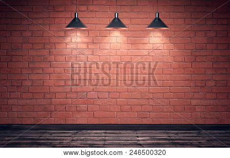 Empty Old Grungy Room With Red Brick Wall And Wooden Floor. Three Hanging Metal Lamps With Direction