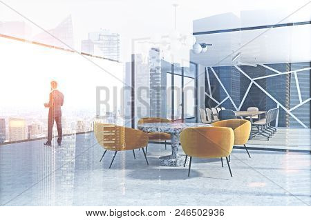 Businessman Standing In A Modern Panoramic Office With A Boardroom And A Waiting Room. 3d Rendering