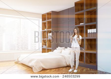 Woman With A Smartphone In A White And Gray Wall Bedroom Corner With A White Bed Standing Between Bo