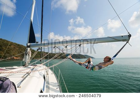 Young and happy sailor relaxes in a hammock set on the boom of the sailing boat anchored in a tropical sea