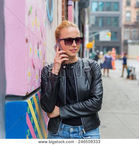 Stylish Woman Talking On Smartphone Leaning Against Colorful Graffiti Wall In East Village, New York