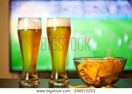 beer glasses and chips in front of tv - football at home - soccer supporters