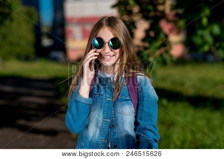Girl Schoolgirl. Summer In Nature. In Hands Holding Smartphone Communicates Over Phone. Smiles Happi
