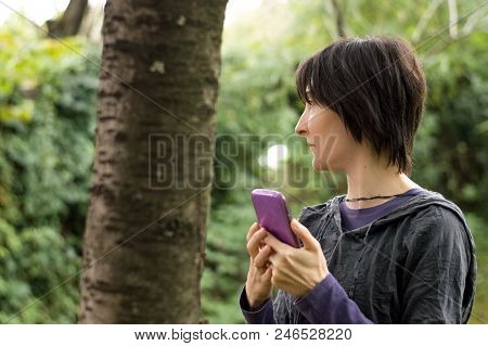 Young Caucasian Woman Using Smartphone In The Forest. Navigation Concept.