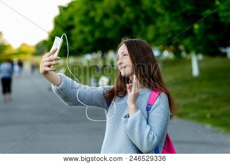 A Teenage Girl After School. In Summer Park On Street. In His Hands Holds Smartphone. Communicate By