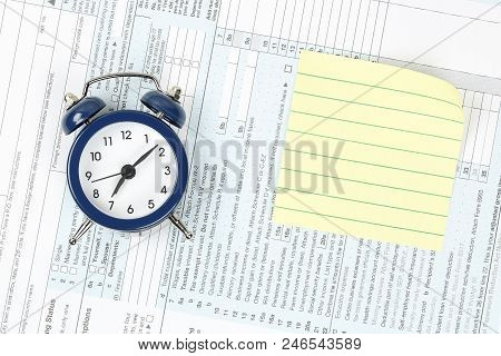 Alarm Clock And Yellow Note On Usa Tax Form