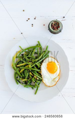 Cooked Green Beans With Sauce Balsamico Glassa And Fried Egg In White Plate On Wooden Background. He