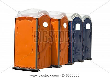 Horizontal Shot Of Four Bright Colored Portable Potties.  Two Are Orange And Two Are Dark Blue.  Iso
