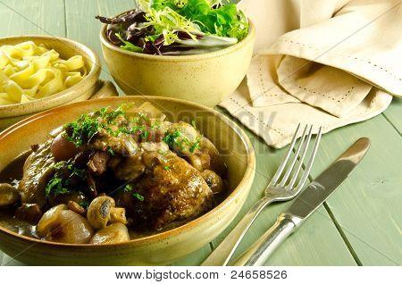 coq au vin with salad and noodles