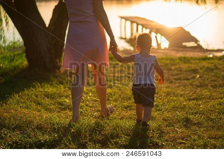 Beautiful Mother Is Walking On The Pier With Her Little Baby Boy With First Steps At Sunset At Summe