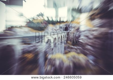 Blur Or Defocused Image Of  Gray, High Bridge With Railway Tracks Leaving Into The Tunnel Above The