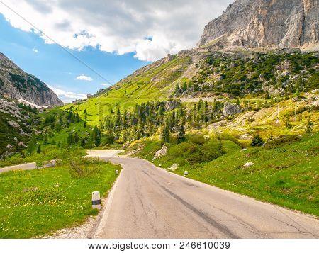 Asphalt Road, Green Meadows And Dolomite Rocks At Passo Falzarego, Dolomites, Italy.