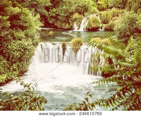 Krka waterfalls. Croatian national park. Beautiful natural scene. Flowing water and greenery. Yellow photo filter. poster
