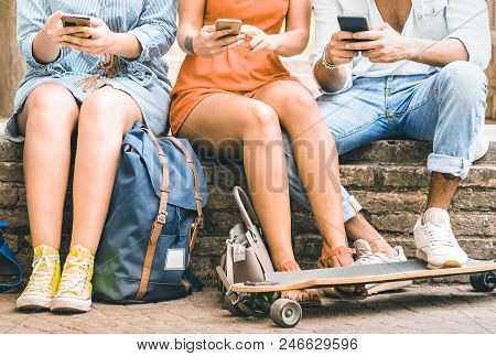 Group Of Millennial Friends Having Fun Spending Time Together With Mobile Smartphones And Skateboard