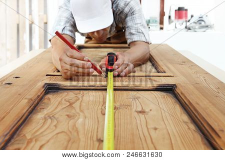 Carpenter At Work Measures With The Tape Measure And Pencil On Wood Background