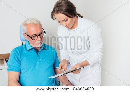 Confident Female Doctor Explaining Paperwork To Senior Male Patient In Medical Clinic. Doctor Explai