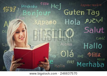 Pretty Girl Holding A Red Book In Front Of A Huge Blackboard Written With The Word Hello In Differen