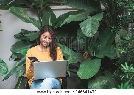 Young Asian Woman Shopping Online With Her Laptop In A Coffee Shop Garden With A Background Of A Gre