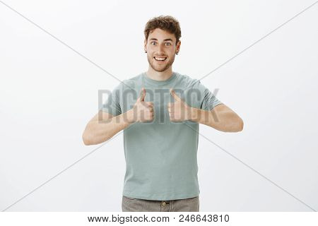 Portrait Of Excited Happy European Guy With Blond Hair In T-shirt, Showing Thumbs Up And Smiling Bro