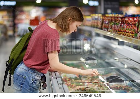 Horizontal Shot Of Adorable Teenage Female Going To Buy Frozen Vegetables, Looks Into Friedge While