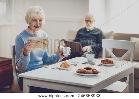 My Youth. Positive Joyful Woman Looking At The Photo While Remembering Her Youth