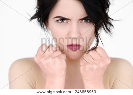 emotion face. angry mad cross woman clenching fists. fury and rage concept. young beautiful brunette girl portrait on white background. poster
