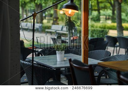 Empty Outdoor Cafe - Elegant Black Furniture Against A Green Park Background. Tables And Chairs At R