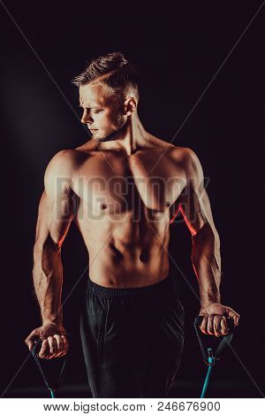 Fitness man exercising with stretching band. Muscular sports man exercising with elastic rubber band. Guy working out with rubber band. Fit, fitness, exercise, workout and healthy lifestyle poster