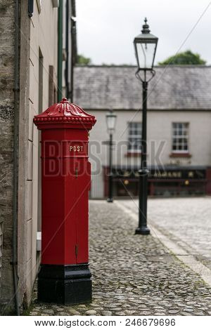 A Bright Red Post Box On An Old Cobbled Street.