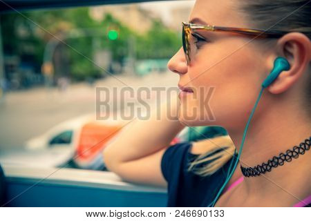 Tourist woman on the bus tour with headphones in ears listening guide, discovering points of interest of Barcelona, active summer vacation in Europe