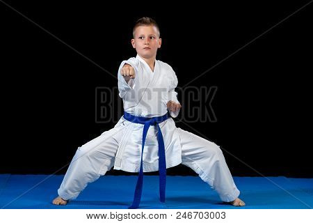 Pre-teen Boy Doing Karate On A Black Background.