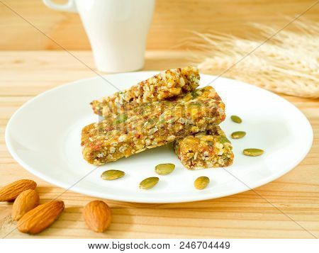 Whole Wheat Cereal Bars Or Flapjacks With Pumpkin Seeds And Dried Fruit On Wooden Table