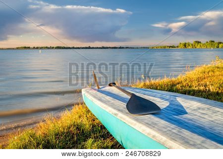 stand up paddleboard with a paddle on a lake shore in Colorado (Boyd Lake State Park), summer scenery