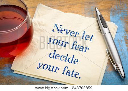 Never let your fear decide your fate - inspiraitonal handwriting on a napkin with a cup of tea