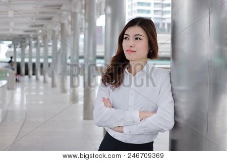 Confident Young Asian Busineswoman Leaning A Pole At Walkway Outside Office. Leader Business Woman C