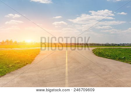 Empty airport taxiway with panoramic blue sky background. Airfield runaway cityscape. poster