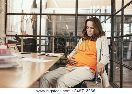 Discomfort Of Pregnancy. Sorrowful Pregnant Ceo Sitting At Table And Looking At Tummy