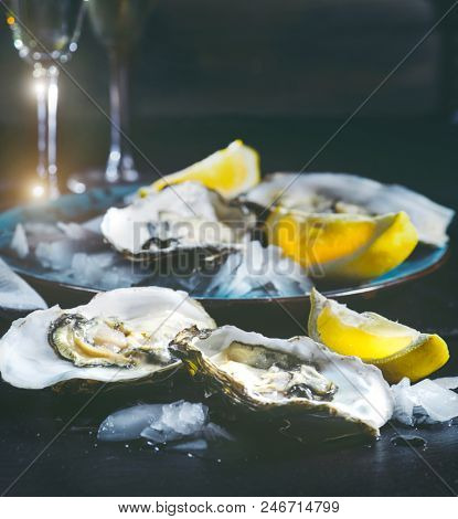 Fresh Oysters close-up on blue plate, served table with oysters, lemon and ice. Healthy sea food. Oyster dinner with champagne in restaurant. Gourmet food