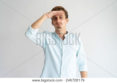 Focused Pensive Curly Guy Imitating Far Away Look. Young Caucasian Blonde Man Keeping Hand At Forehe