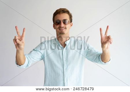 Happy Careless Guy Ready For Summer Vacation. Positive Young Caucasian Man Wearing Sunglasses Showin