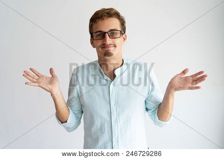 Smiling Careless Blonde Guy Showing Do Not Know Gesture. Young Caucasian Man In Glasses Throwing Up