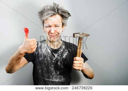 Unshorn In Construction Dust Young Guy With Hammer And Sick Finger From Blow, On Gray Background.