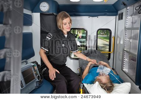 Female EMT worker showing care to senior woman patient inside ambulance