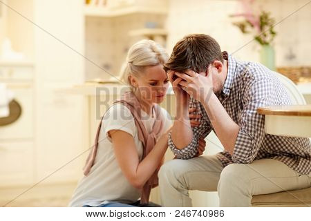Young woman comforting her unhappy and desperate husband after saying bad news