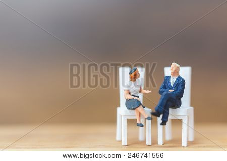 Miniature People Thinking About Next Great Idea On Wooden Background
