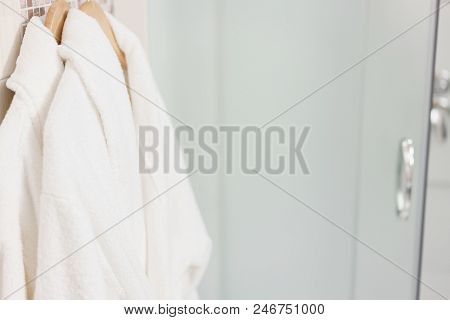 Bathroom Inside rooms of a apartment or hotel. Clean white towel and bathrobe on a hanger prepared to use poster