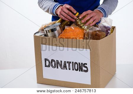 Food In A Donation Cardboard Box, Isolated On White Background, Volunteer Fills The Box.