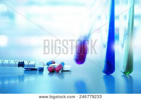 green blue purple biochemistry agar in test tube with syringe and pill capsule of drug in medical health science research laboratory background poster